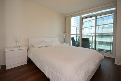 Spacious Sized Master Bedroom With A Large Mirrored Closet, Laminate Flooring Throughout & A Walk-Out Balcony.
