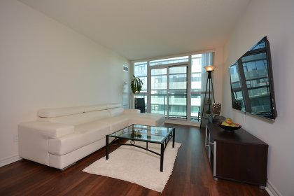 Bright Floor-To-Ceiling Windows With Laminate Flooring Throughout With Balcony City & Lake Views.