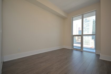 Spacious Sized Master Bedroom With Mirrored Closets & Plank Laminate Flooring.