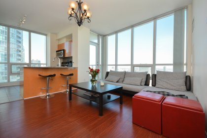 Bright Floor-To-Ceiling Windows With Laminate Flooring Throughout The Living & Dining Areas.