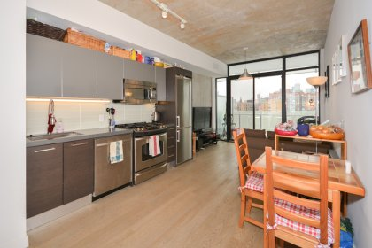 Kitchen Area With Exposed Concrete Ceiling, Bright Floor-To-Ceiling Windows & Hardwood Flooring Facing Unobstructed C.N. Tower & Stanley Park Views.