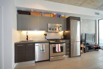 Designer Kitchen Cabinetry With Stainless Steel Appliances, A Gas Stove, Glass Tile Backsplash, Quartz Counter Top, Undermount Valance Lighting & Unde