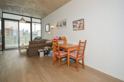 Dining Area With Exposed Concrete Ceiling, Bright Floor-To-Ceiling Windows & Hardwood Flooring Facing Unobstructed C.N. Tower & Stanley Park Views.