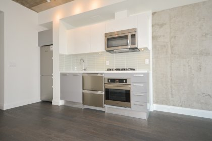 Designer Kitchen Cabinetry With Stainless Steel Appliances, A Glass Tile Backsplash, An Undermount Sink & A Gas Stove.