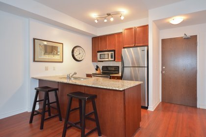 Designer Kitchen Cabinetry With Stainless Steel Appliances, An Undermount Sink, Granite Counter Tops & A Breakfast Bar.