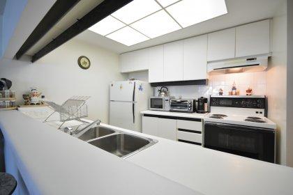 Kitchen With Ceramic Tile Backsplash & A Breakfast Bar.