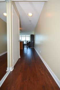 Suite Foyer With Mirrored Closets & Hardwood Flooring Throughout.