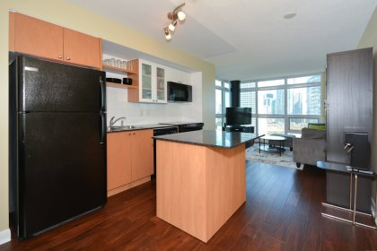 Designer Kitchen Cabinetry With Granite Counter Tops & A Mobile Breakfast Bar.