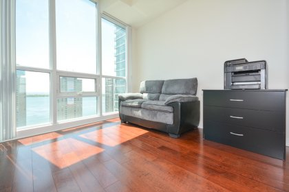 2nd Bedroom With Gleaming Hardwood Flooring, Mirrored Closets & Wrap Around Windows Facing Lake Views.