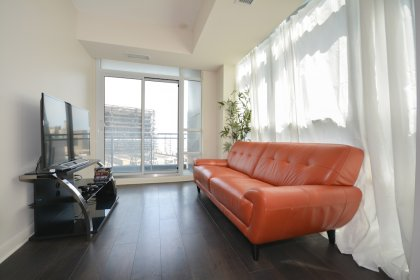 Living Area With Bright Floor-To-Ceiling Windows & Hardwood Flooring Facing Balcony C.N. Tower Views.