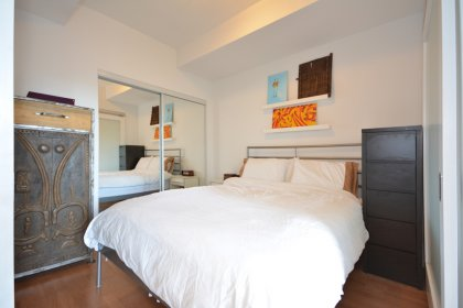 A Spacious Sized Master Bedroom With Hardwood Flooring, Upgraded Privacy Frosted Glass Sliding Doors & A Large Mirrored Closet.
