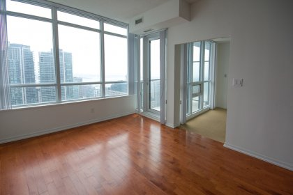 Bright Living / Dining Areas With Hardwood Flooring Facing City & Lake Views.
