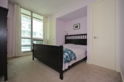 A Spacious Sized Master Bedroom With Double Closets & A Large Window.