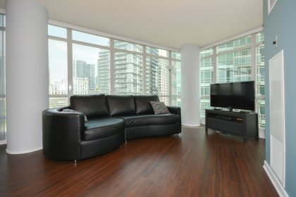 Bright Floor-To-Ceiling Wrap Around Windows With Laminate Flooring Throughout The Living Area.
