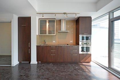 Designer Kitchen Cabinetry With Stainless Steel Appliances, Granite Counter Tops, Undermount Sink & Glass Tile Backsplash.