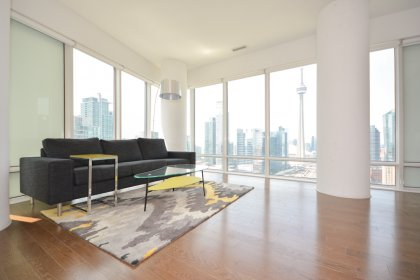 Bright Floor-To-Ceiling Wrap Around Windows With Hardwood Flooring Facing Unobstructed C.N. Tower & City Views.