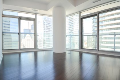 Living Area With Bright 9' Floor-To-Ceiling Wrap Around Windows & Hardwood Flooring.