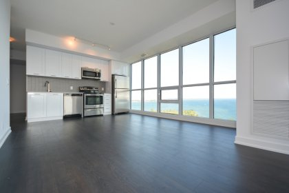 Bright Floor To Ceiling Windows With Laminate Flooring Throughout & A Large Private Balcony Overlooking Unobstructed Lake Views.