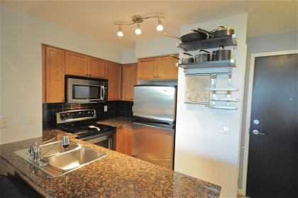 Designer Kitchen Cabinetry With Stainless Steel Appliances, Granite Counter Tops & Ceramic Backsplash.