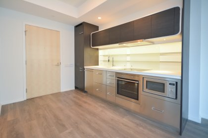 Designer Kitchen Cabinetry With Stainless Steel Appliances, Corian Counter Top, Glass Shelving and Laminate Flooring Throughout.