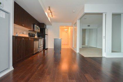 Bright Floor-To-Ceiling Windows With Hardwood Flooring Facing Inner Court Yard Views.