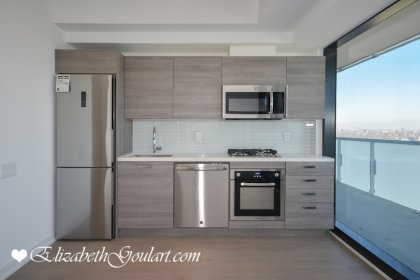 Designer Kitchen Cabinetry With Stainless Steel Appliances, Gas Range, Stone Counter Top & An Undermount Sink.