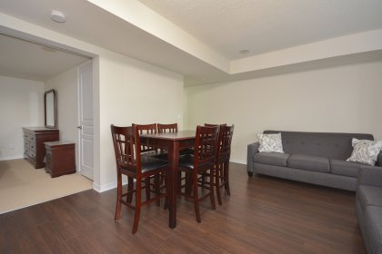 Living & Dining Areas With Bright Floor-To-Ceiling Windows With Laminate Flooring Throughout.
