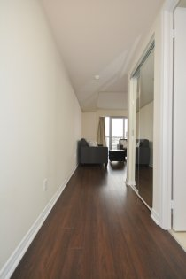 Suite Foyer With Hardwood Flooring & A Mirrored Closet.
