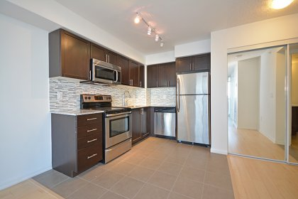 Designer Kitchen Cabinetry With Stainless Steel Appliances, Granite Counter Tops, An Undermount Sink & Tiled Backsplash.
