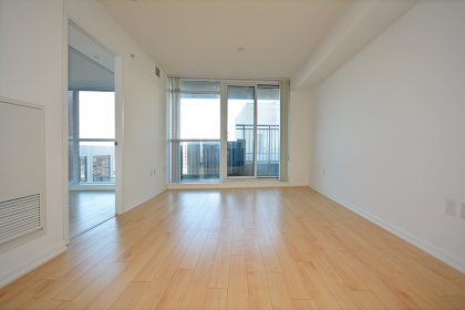 Living & Dining Area With Bright Floor-To-Ceiling Windows With Laminate Flooring Throughout Facing Unobstructed East Views.