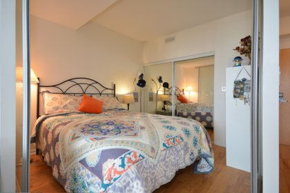 Spacious Sized Master Bedroom With Hardwood Flooring & A Large Mirrored Closet.