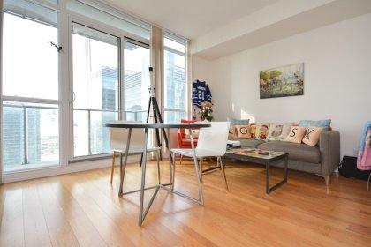 Living and Dining Areas With Bright Floor-To-Ceiling Windows & Hardwood Flooring Throughout Facing C.N. Tower Views.
