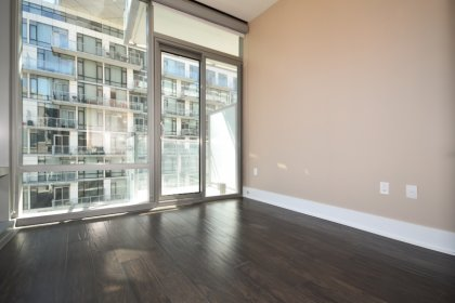 2nd Bedroom With Wrap Around Windows, Hardwood Flooring & A Walk-Out Balcony Facing The Outdoor Pool / Lake Views.