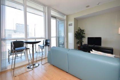 Bright Floor-To-Ceiling Windows With Hardwood Flooring.