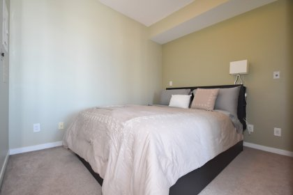 Spacious Sized Master Bedroom With A Mirrored Closet & A Glass Sliding Door.