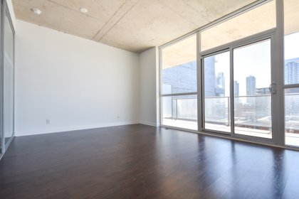 Bright Floor-To-Ceiling Windows With Laminate Flooring Facing City Views.