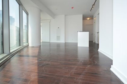 Bright Floor-To-Ceiling Wrap Around Windows With Gleaming Hardwood Flooring Facing Lake Views.