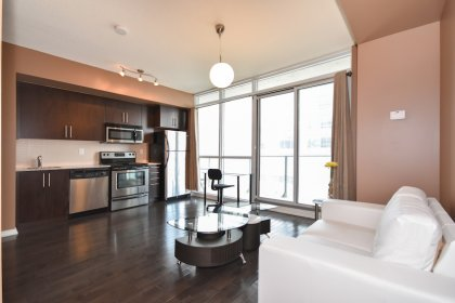 Bright Floor-To-Ceiling Windows With Gleaming Hardwood Flooring & Balcony C.N. Tower Views.