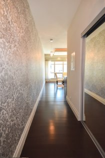 Suite Foyer With A Mirrored Closet, Designer Wall Coverings & Gleaming Hardwood Flooring Throughout.