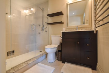 A Spa Bath With A Pocket Door & A 3-Piece Including A Frameless Glass Stand-Up Shower, Heated Towel Rack & Flooring.