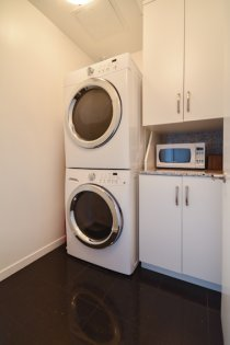 A Laundry Area With Granite Counter Top, Additional Storage Cabinetry & Upgraded Full-Sized Stacked Washer & Dryer.