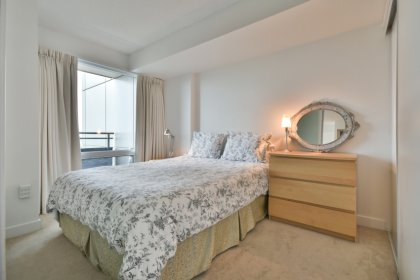 A Spacious Sized Master Bedroom With A Frosted Glass Sliding Door, A Large Window  & Large Closet.