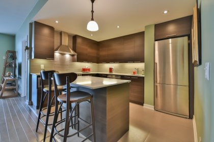 Designer Kitchen Cabinetry With Stainless Steel Appliances, Wine Fridge, Granite Counter Tops, Tile Backsplash, An Undermount Sink & Valance Lighting.