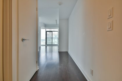 Suite Foyer With Hardwood Flooring & Mirrored Closet.
