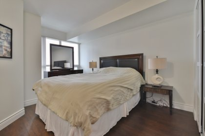 Master Bedroom With Laminate Flooring, Upgraded Closet Doors & A Large Window Facing C.N. Tower Views.