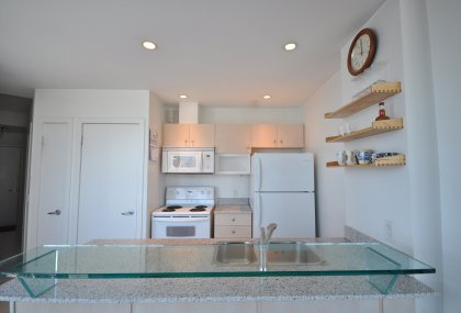 Designer Kitchen Cabinetry With Granite Counter Tops, Pot Lighting, A Glass Breakfast Bar & Marble Flooring.