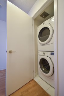 Laundry Area With A Stacked Full Sized Washer/Dryer.