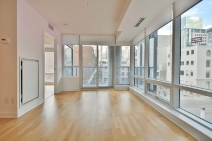 Bright Open Concept Living & Dining Areas With Floor-To-Ceiling Wrap Around Windows, Hardwood Flooring With C.N. Tower Views.