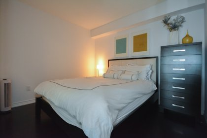 2nd Bedroom With Glass Sliding Doors, Mirrored Closet & Hardwood Flooring Throughout.