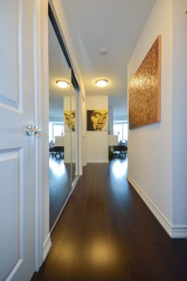 Suite Foyer With Hardwood Flooring Throughout & A Mirrored Closet.